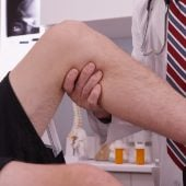 Senior caucasian doctor examining knee injury