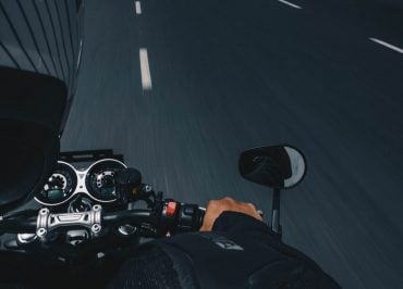 Zoom shot of a motoryclist driving with a helmet